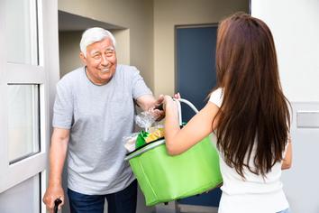 Äleterer Herr erhält seine Einkäufe nach Hause geliefert.