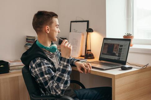 Jugendlicher an einem Laptop