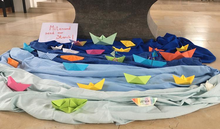 Origami-Segelboote auf einem See aus Tüchern.