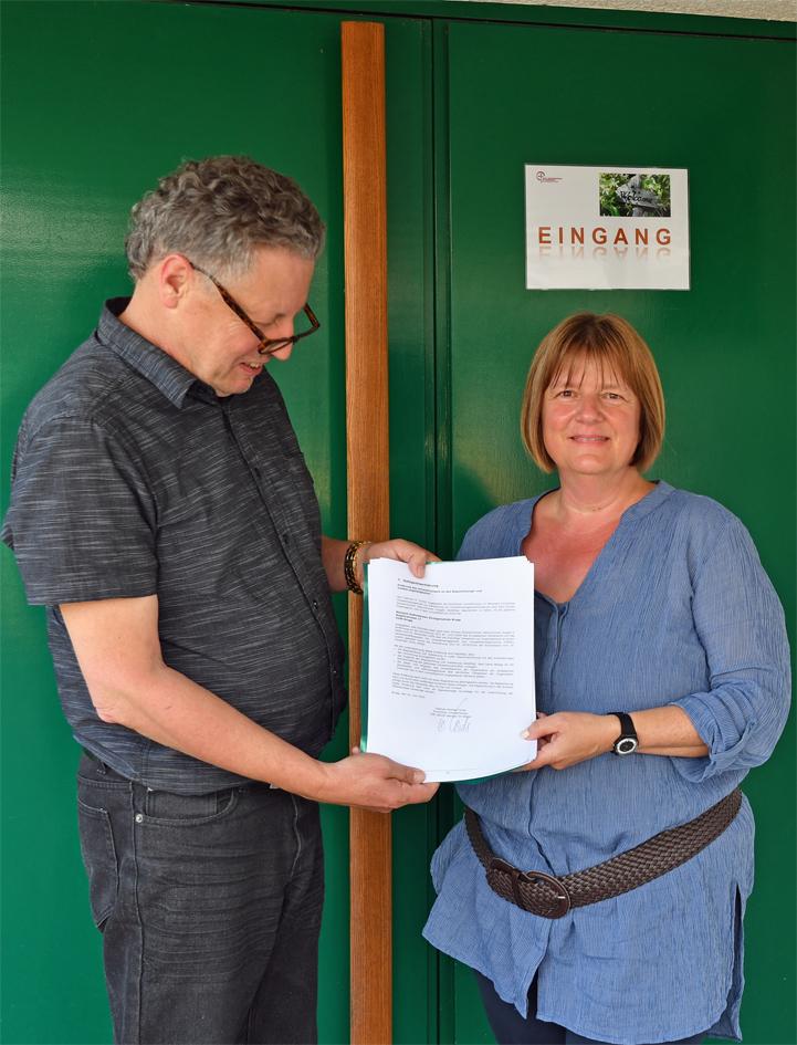 Iris Bäriswyl und Dietmar Cords präsentieren den unterschriebenen Prüfbericht.