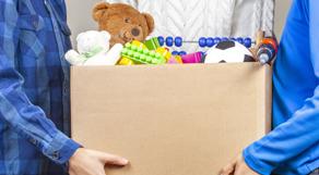 Zwei Kinder tragen eine Schachtel mit Spielzeug.