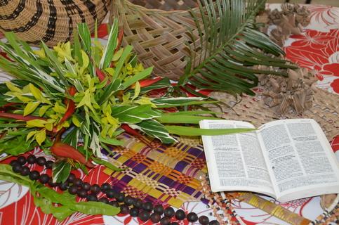Aufgeschlagene Bibel neben typischen Gegenständen aus Vanuatu.