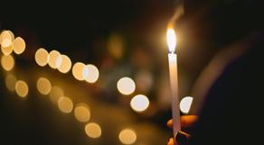 Menschen halten in der Dunkelheit eine Kerze.