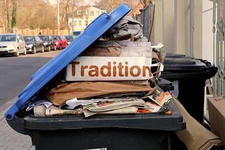 Karton mit der Aufschrift Tradition in einem Abfallcontainer.
