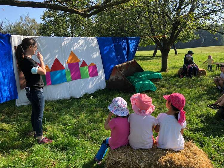 Kinder und Erwachsene sitzen auf Heuballen im Obstgarten eines Bauernhofes.